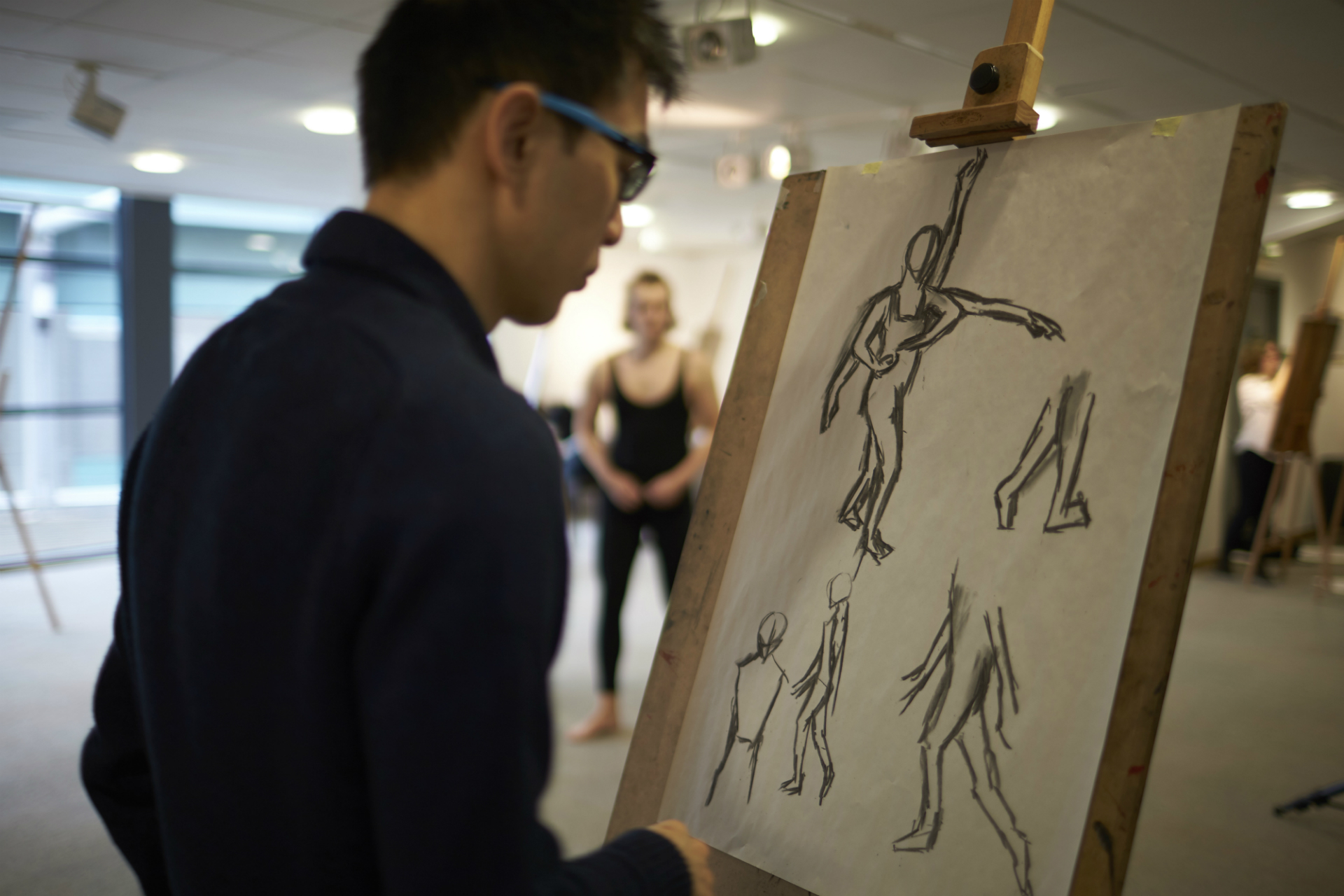 Male Drawing Using An Easel   Live Model In Background